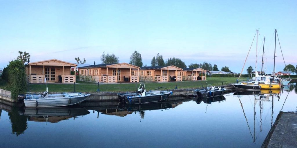 Cabins laying close to the water with aluminum boats dock in front of them.